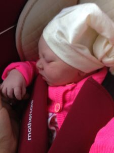 A newborn baby wearing bright pink with a white hat, sleeping in a car seat.
