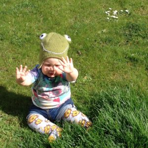 Baby wearing a green frog hat and jeans shorts with a t-shirt, holding up her hands while sitting on the grass