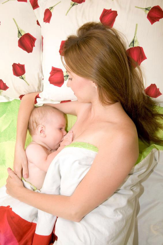 A brown haired lady, lying on her side, on a bed, breast feeding her baby who is also lying on the bed.