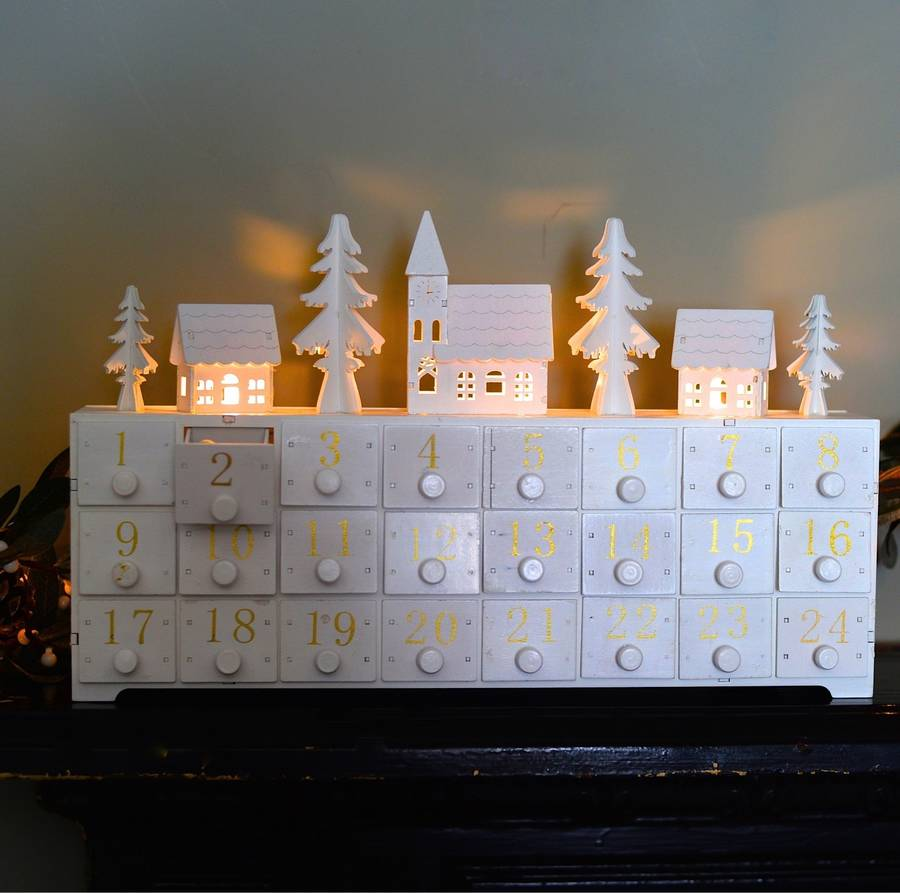 White chest with 3 rows of 8 box drawers with gold numbers on each drawer from 1 -24. with white lit up tree and house ornaments on top
