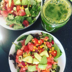2 bowls of salad with tomato, sweetcorn, lettuce avocado and a mason jar of green juice.