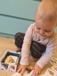 Young toddler picking up a card on the floor amongst others